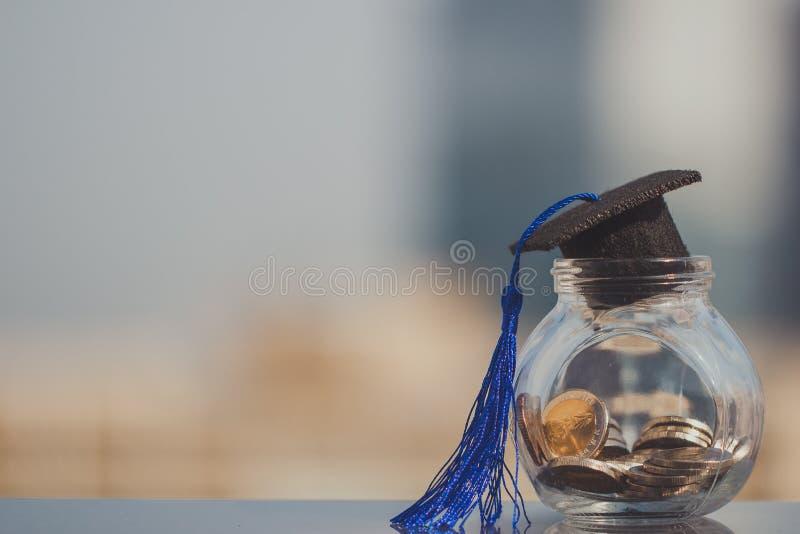 Cappello di graduazione sui soldi delle monete nella bottiglia di vetro su fondo bianco immagine stock libera da diritti