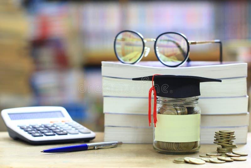Cappello di graduazione sulla bottiglia di vetro sullo scaffale per libri nella biblioteca r fotografie stock