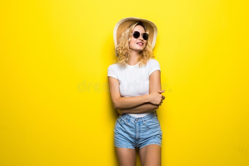 Cappello di paglia d'uso della giovane donna del ritratto che posa sopra il fondo giallo variopinto fotografie stock libere da diritti