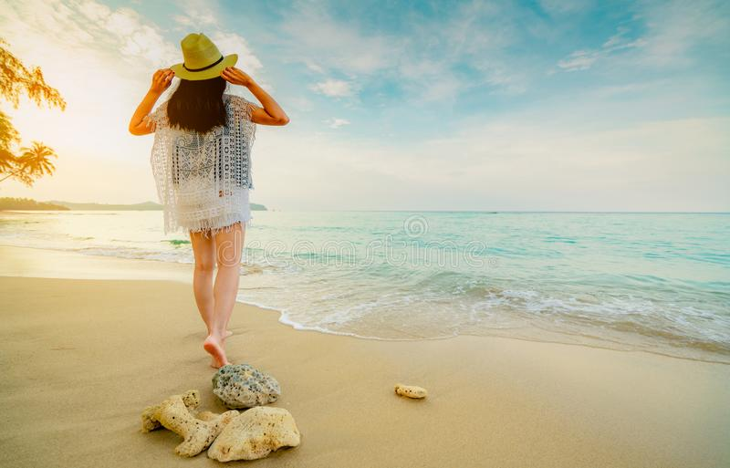 Cappello di paglia felice di usura di giovane donna che cammina sulla spiaggia Rilassandosi e godere della festa alla spiaggia tr immagine stock