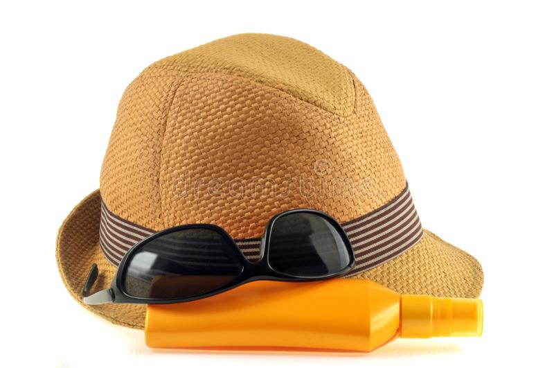 Cappello di paglia, occhiali da sole e protezione solare su un fondo bianco immagine stock libera da diritti