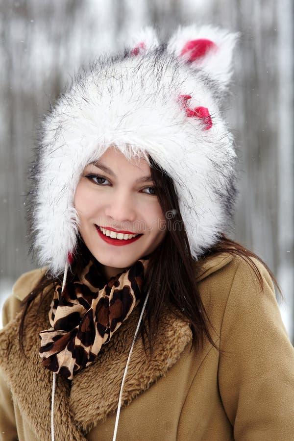 Cappello di pelliccia d'uso della bella donna nella foresta nell'inverno immagine stock libera da diritti