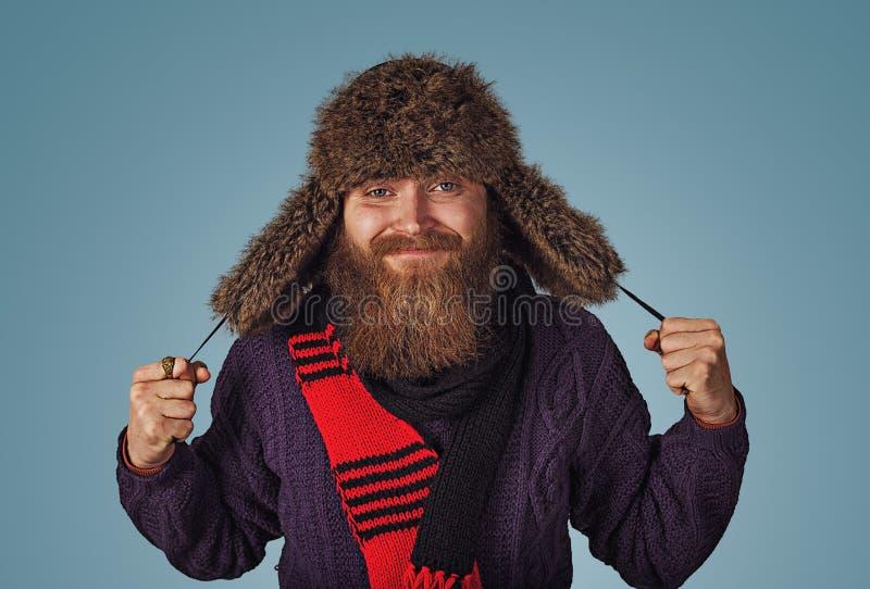 Cappello di pelliccia lanuginoso di rappresentazione della tenuta dell'uomo in maglione porpora della sciarpa rossa fotografia stock libera da diritti