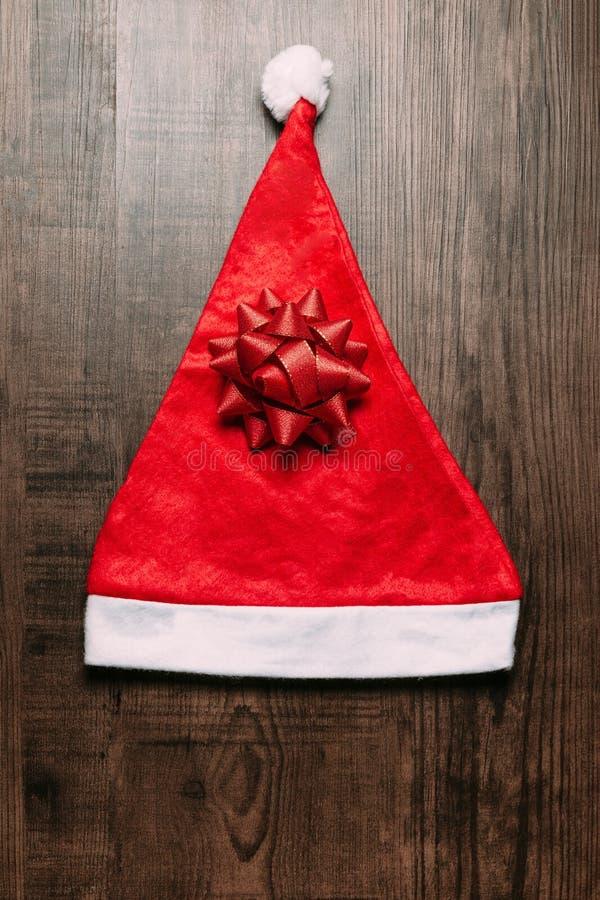 Cappello di Santa con il nastro rosso su fondo di legno Disposizione piana per il Natale e l'insegna del buon anno fotografia stock libera da diritti