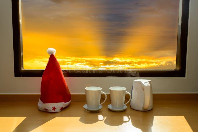 Cappello di Santa con la tazza da caffè vicino alla finestra immagini stock