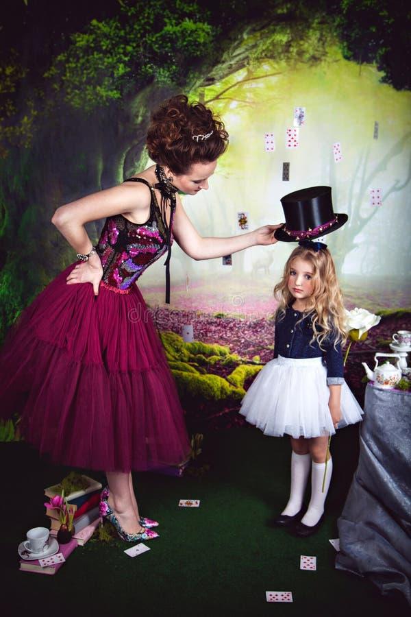 Cappello diabolico della tenuta della regina sopra piccola Alice immagini stock libere da diritti