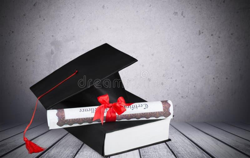 Cappello e libro di graduazione fotografia stock
