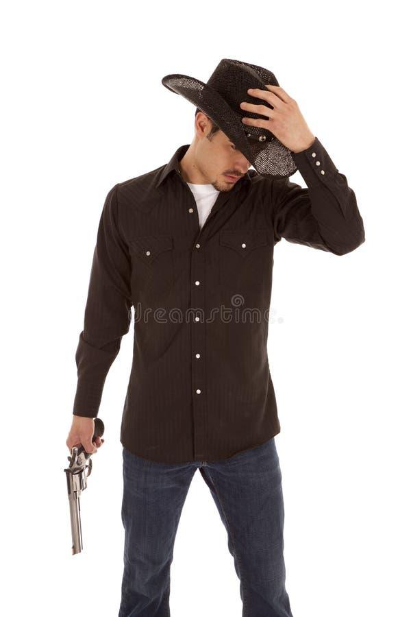 Cappello e pistola della holding del cowboy fotografia stock libera da diritti