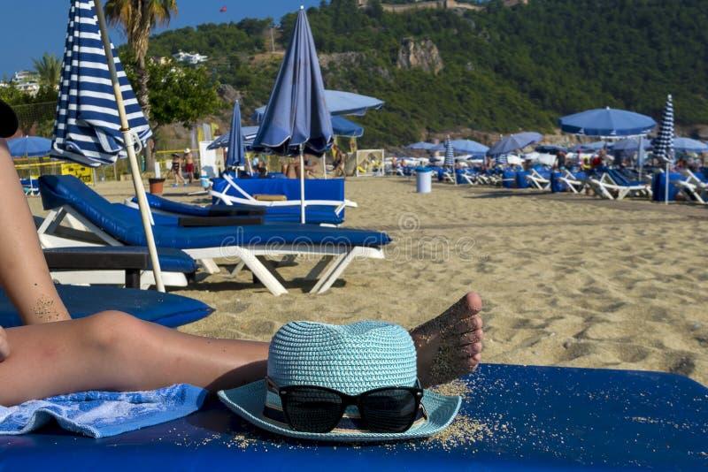 Cappello e vetri sui precedenti della spiaggia Un uomo sta trovandosi su una chaise-lounge del sole fotografie stock