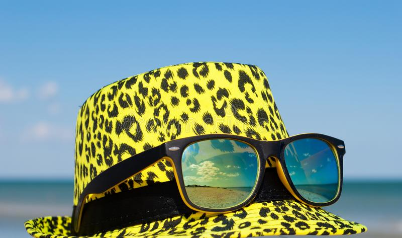 Cappello giallo luminoso con la lente gialla del camaleonte di vetro su un fondo di cielo blu con la riflessione di vetro del mar fotografia stock libera da diritti