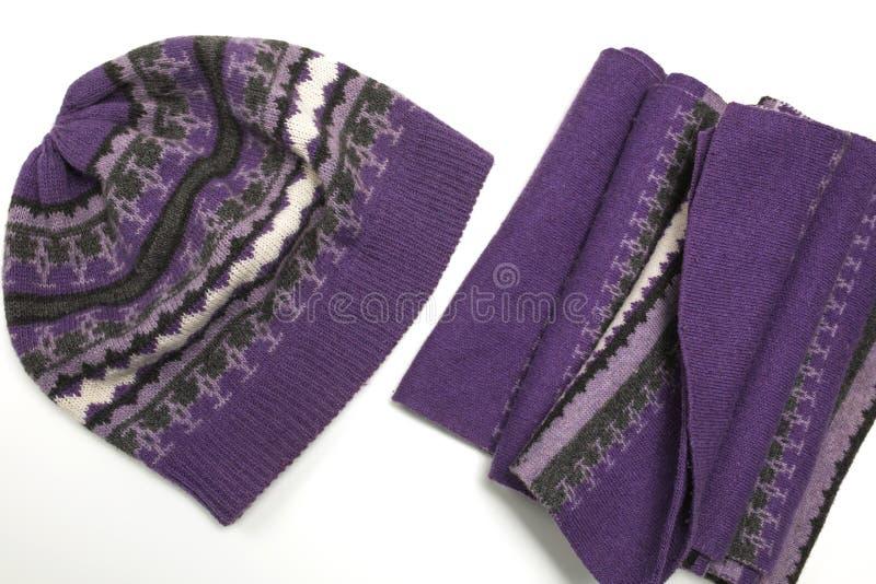 Cappello tricottato e sciarpa porpora isolati su fondo bianco immagine stock