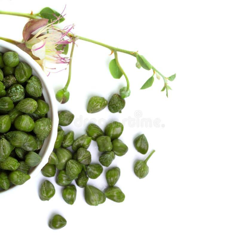 Capperi con le foglie verdi ed il fiore in ciotola bianca fotografie stock libere da diritti