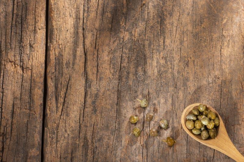 Capperi in cucchiaio di legno - capparis spinosa Fondo di legno fotografia stock