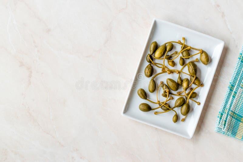 Capperi marinati ed inscatolati pronti da mangiare in piatto immagini stock