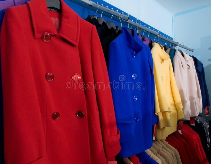 Cappotti femminili di autunno variopinto in negozio fotografia stock