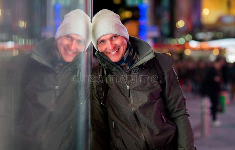 Cappotto d'uso bello e cappello del giovane su fondo con le luci vaghe della città alla notte fotografia stock libera da diritti