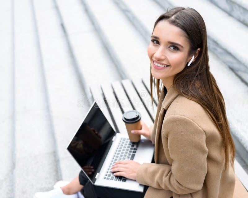 Cappotto d'uso di autunno della bella giovane donna facendo uso del computer portatile immagini stock