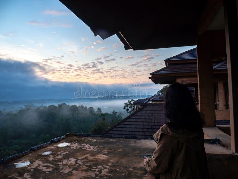 Cappotto e condizione di marrone di usura di donne sul balcone E sguardo fuori con la foresta e la foschia di mattina Il sole dor fotografia stock libera da diritti