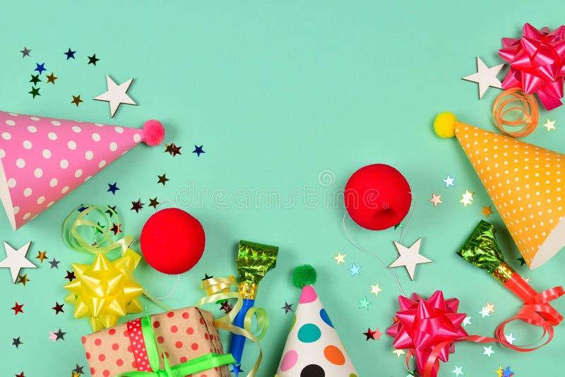 Cappucci di compleanno, presente, coriandoli, nastri, stelle, nasi del pagliaccio su un fondo verde Spazio per testo o progettazi fotografia stock