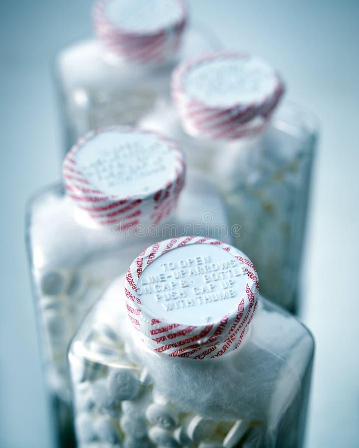 Cappucci di sicurezza sulle bottiglie sigillate delle pillole di aspirin comunemente usate come farmaco di sollievo dal dolore ed fotografia stock libera da diritti