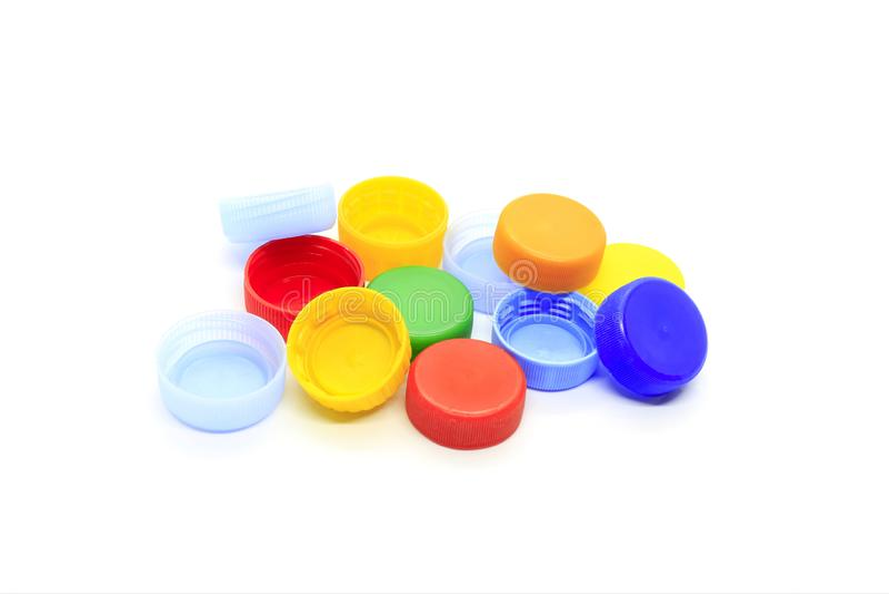 Cappucci multicolori dalle bottiglie di plastica su fondo bianco fotografia stock