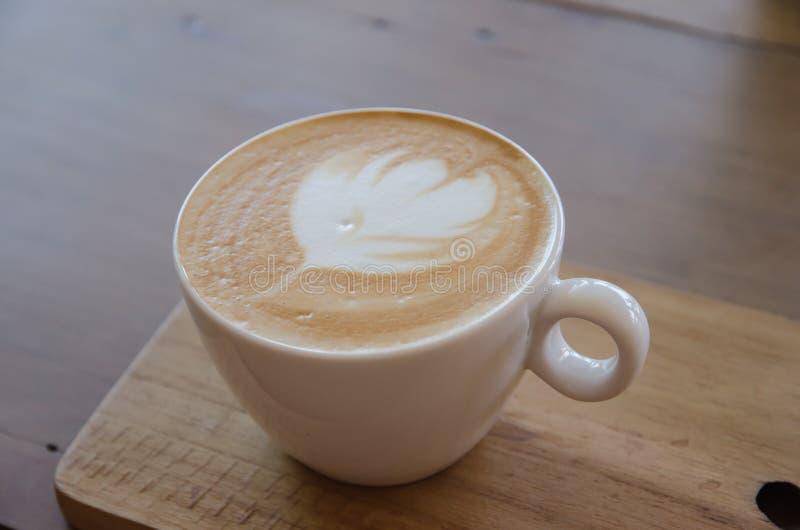 Cappuccino über Holztisch lizenzfreie stockfotografie