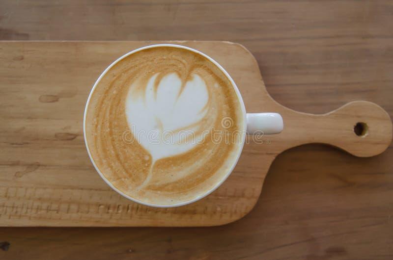 Cappuccino über Holztisch lizenzfreies stockfoto
