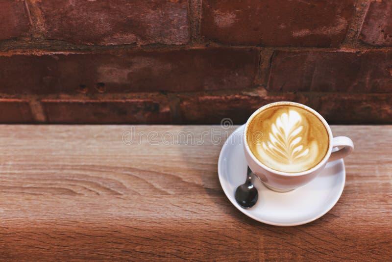 Cappuccino στον πίνακα κοντά στο τουβλότοιχο στοκ εικόνα