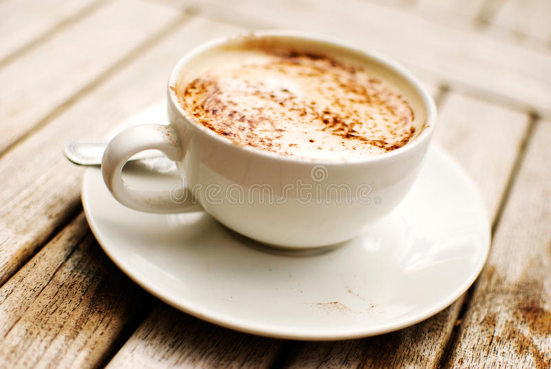 Cappuccino. Cup of cappuccino over wooden table stock images