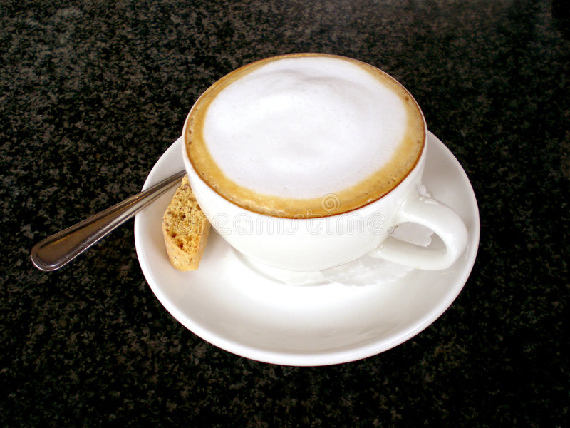 Cappuccino. A full white cup of a delicious Italian skinny (low fat) Cappuccino with spoon and cookie standing on a black granite table of a coffee shop outdoors stock image