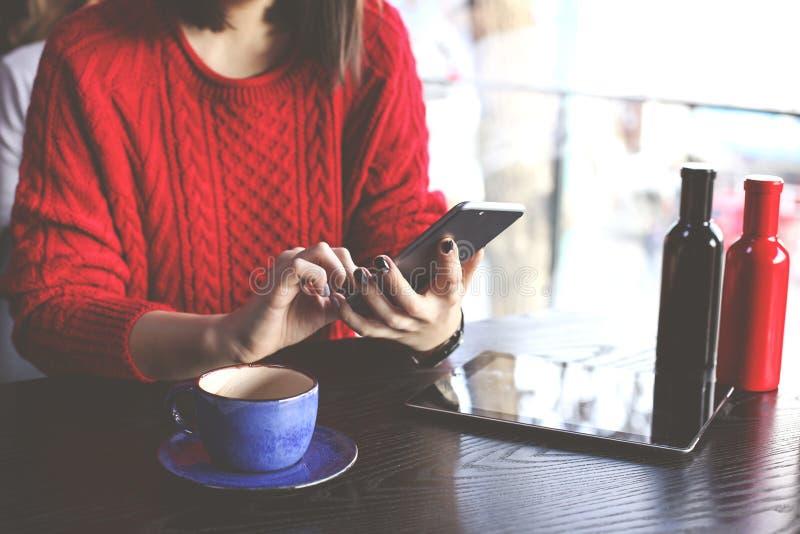 Cappuccino bebendo da jovem mulher feliz, latte, macchiato, chá, usando o tablet pc e falando no telefone em uma cafetaria/vagabu imagem de stock royalty free