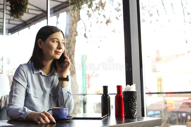 Cappuccino bevente della giovane donna felice, latte, macchiato, tè, facendo uso del computer della compressa e della conversazio fotografie stock