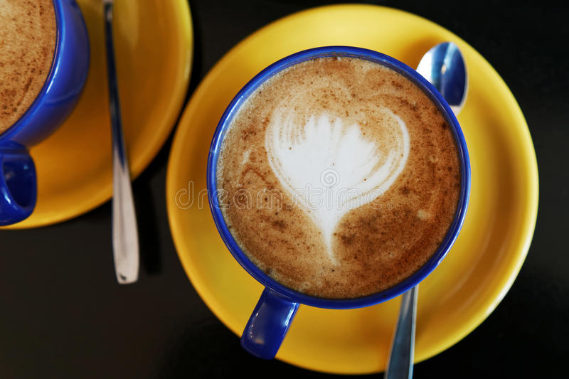 Cappuccino in a blue cup on a yellow saucer royalty free stock photos
