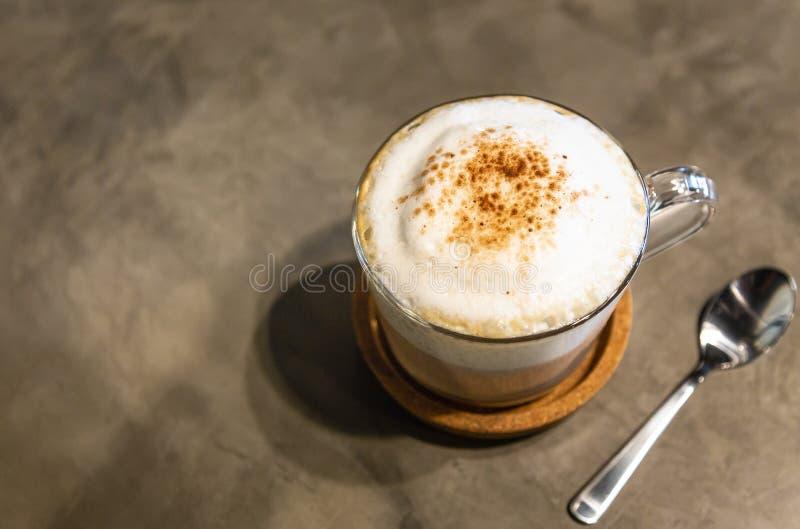 Cappuccino caldo del caffè con la copertura della schiuma della schiuma del latte sulla cima, spruzzata con cioccolato in polvere fotografie stock libere da diritti
