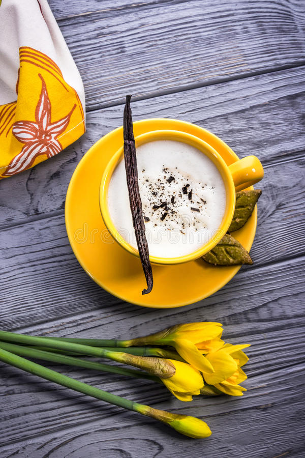 Cappuccino caseiro e narcisos amarelos da baunilha no fundo de madeira fotografia de stock