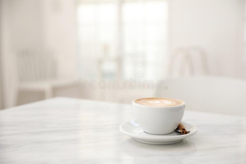 Cappuccino coffee cup on white marble table royalty free stock images