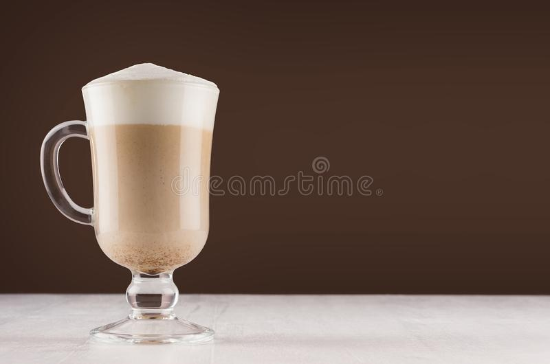 Cappuccino coffee in elegant glass with foam on white table and dark brown wall, copy space. Cappuccino coffee in elegant glass with foam on white table and royalty free stock photo