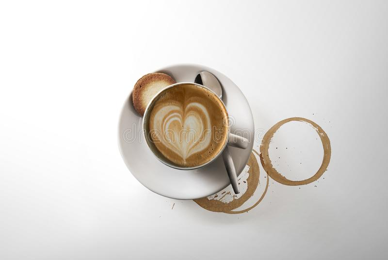 Cappuccino coffee, on a saucer, with a spoon, shot from above on white, with a drop shadow stock photography