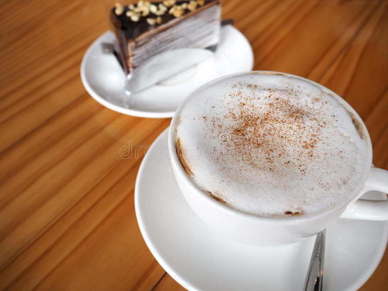 Cappuccino coffee in white cup with chocolate crepe cake on wood royalty free stock photo