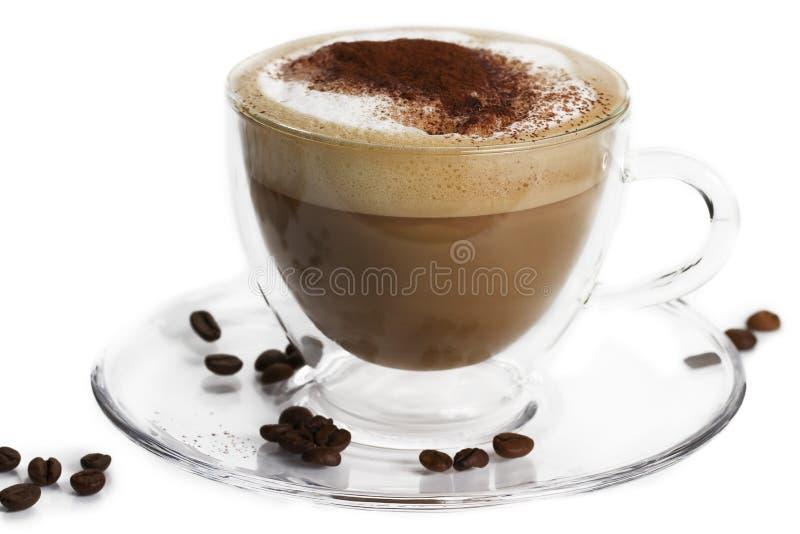 Cappuccino com pó de cacau e feijões no branco fotografia de stock royalty free