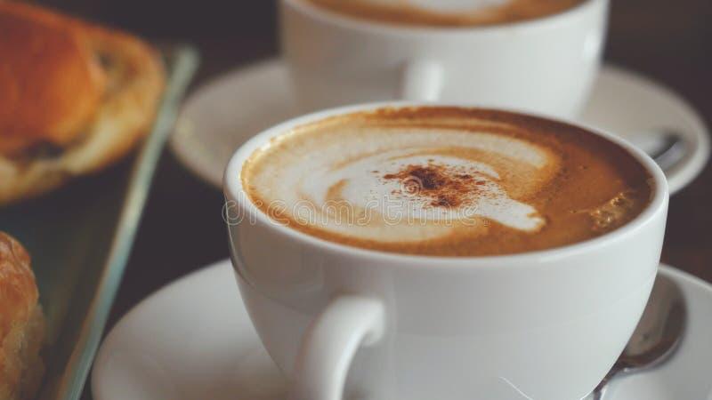 Cappuccino com um rolo francês para o café da manhã fotos de stock