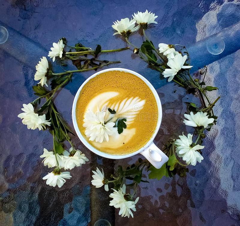 Cappuccino cup with latte art with a rosette. The drawing on coffee. Vigorous drink. White daisies. Flowers. royalty free stock photos
