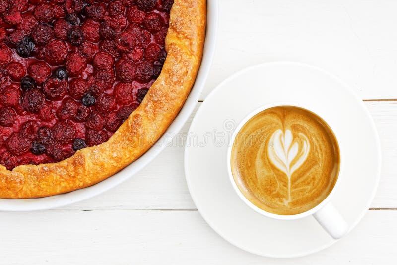 Cappuccino da xícara de café do close up e galette caseiro com framboesas vermelhas e os corintos pretos na tabela de madeira bra fotos de stock royalty free