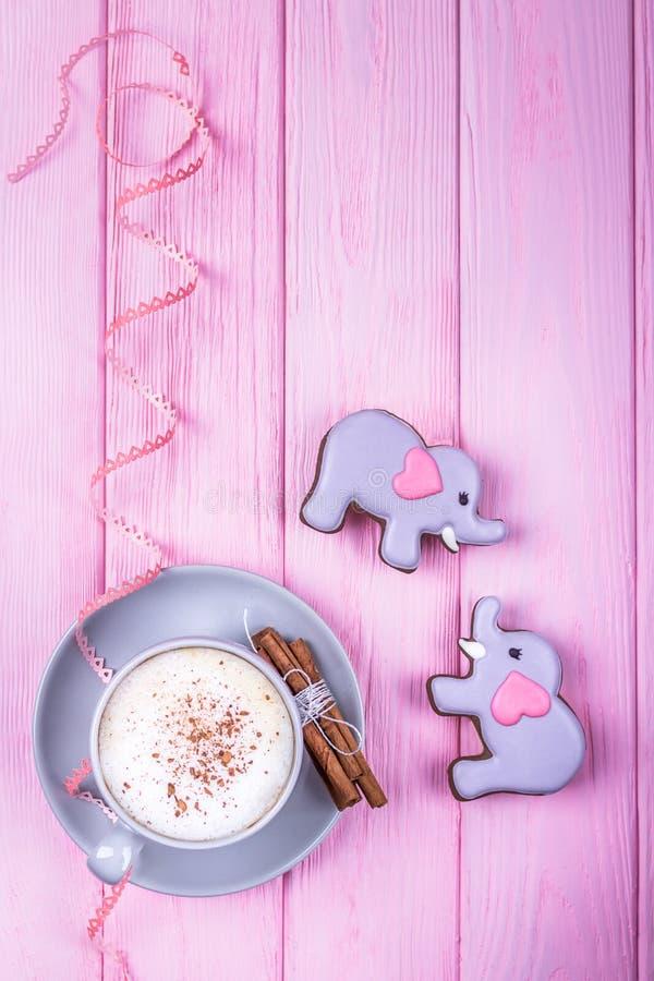 Cappuccino del caffè con gli elefanti del pan di zenzero e della cannella con i cuori su un fondo di legno grigio Giorno felice d fotografie stock