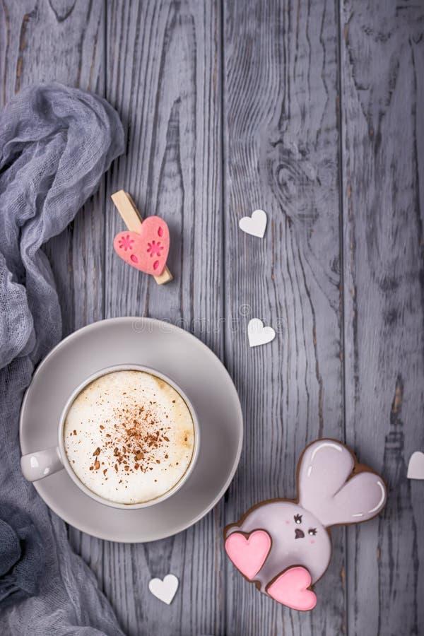 Cappuccino del caffè con il coniglio del pan di zenzero e della cannella con cuore su un fondo di legno grigio Giorno felice del  immagini stock