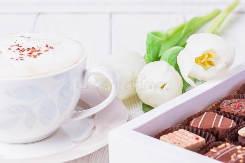 Cappuccino del caffè con la cannella del Ceylon, la caramella di cioccolato di lusso ed i tulipani bianchi su un fondo bianco immagine stock