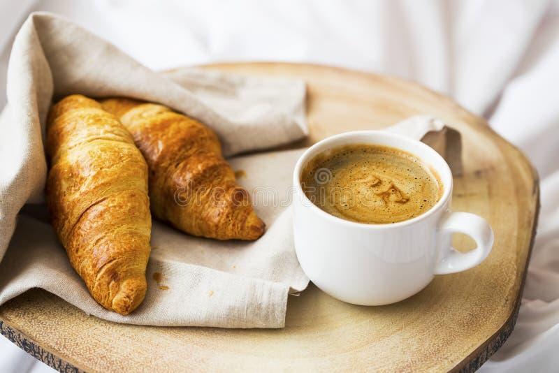 Cappuccino della tazza di caffè con crema ed i croissant al forno saporiti Breafast di mattina con i panini ed il caffè dei crois fotografie stock libere da diritti