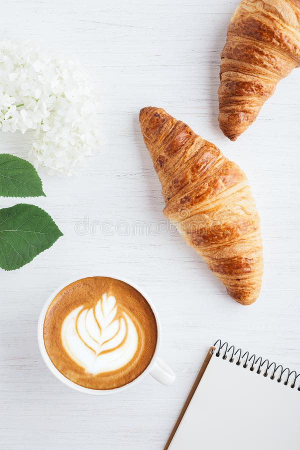 Cappuccino, deux croissants et carnet photo libre de droits