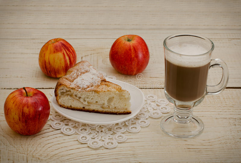 Cappuccino, dojrzali jabłka i jabłczany kulebiak na białym drewnianym tle, fotografia stock