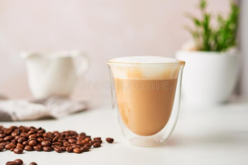 Cappuccino in a double walled glass. With roasted coffee beans. Feminine rose background with copy space. High resolution image, narrow depth of field stock image